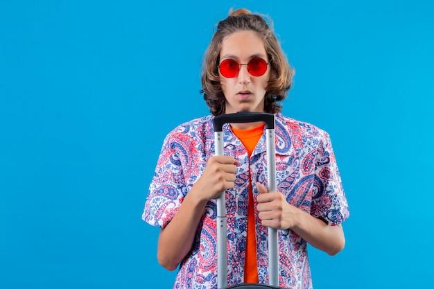 Jonge knappe kerel die rode zonnebril draagt die reiskoffer houdt die verward zich over blauwe achtergrond bevindt