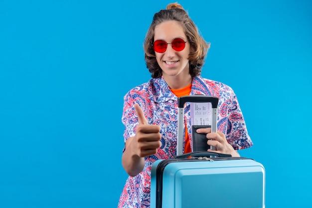 Jonge knappe kerel die rode zonnebril met reiskoffer draagt die luchtkaartjes houdt die duimen omhoog gelukkig en positief glimlachend vrolijk permanent over blauwe achtergrond tonen