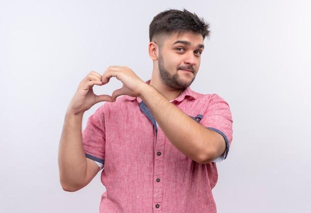 Jonge knappe kerel die roze poloshirt draagt dat cutely doet liefde singh met handen kijkt die zich over witte muur bevinden