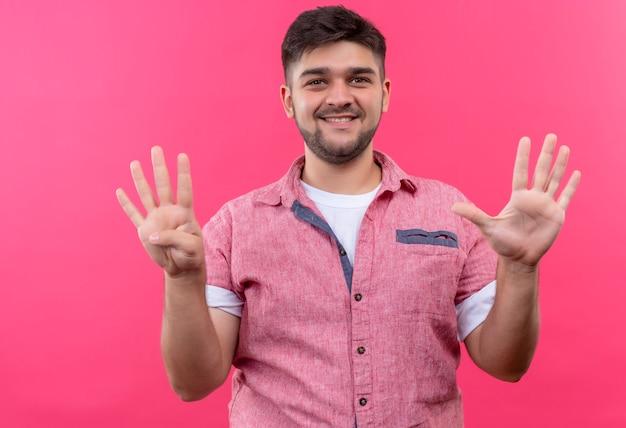 Jonge knappe kerel die roze poloshirt draagt dat gelukkig negen teken met vingers toont die zich over roze muur bevinden