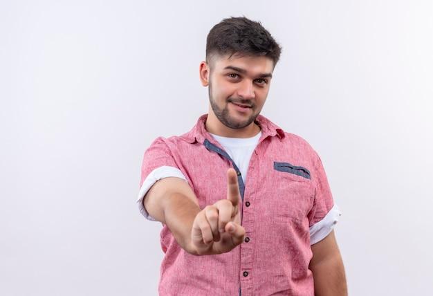 Jonge knappe kerel die roze poloshirt draagt dat met wijsvinger glimlacht die verbod toont dat zich over witte muur bevindt