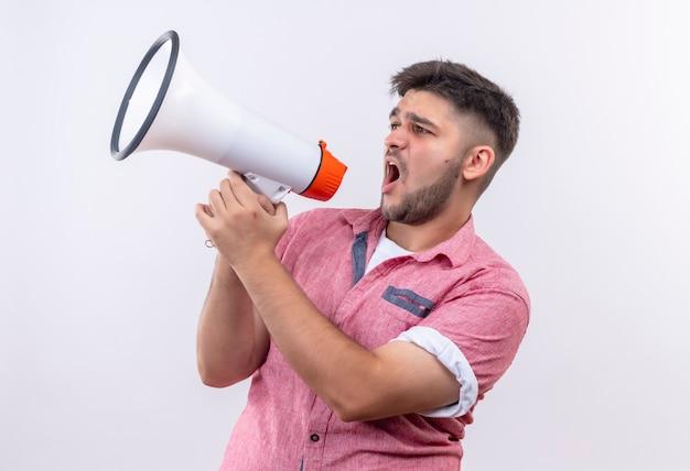 Jonge knappe kerel die roze poloshirt draagt dat op megafoon schreeuwt die naast status over witte muur kijkt