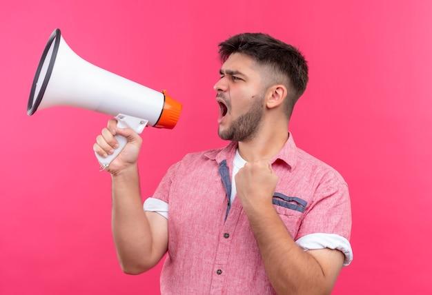 Jonge knappe kerel die roze poloshirt draagt dat op megafoon schreeuwt die zich over roze muur bevindt