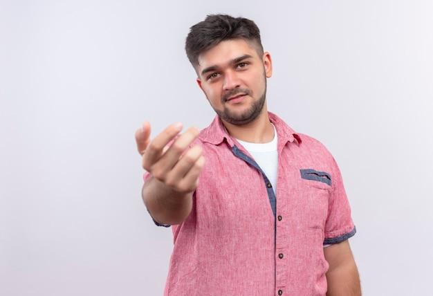 Jonge knappe kerel die roze poloshirt draagt die hem hartelijk roept die zich over witte muur bevindt