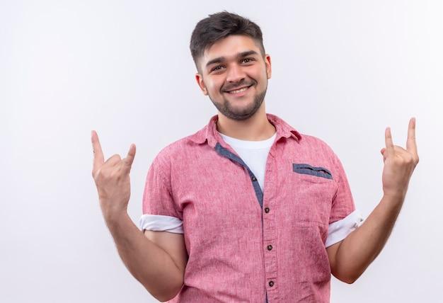 Jonge knappe kerel die roze poloshirt draagt die rots voor altijd ondertekenen met vingers die gelukkig status over witte muur kijken