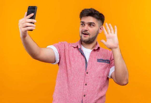 Jonge knappe kerel die roze poloshirt draagt die selfie maakt en hallo zegt die zich over oranje muur bevindt