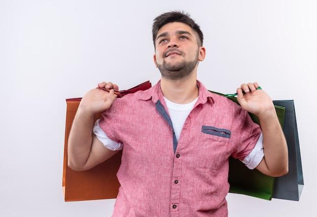Jonge knappe kerel die roze poloshirt draagt die tevreden boodschappentassen in zijn rug houdt die zich over witte muur bevinden
