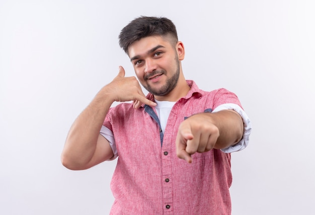 Jonge knappe kerel die speels roze poloshirt draagt, bel me teken dat zich over witte muur bevindt