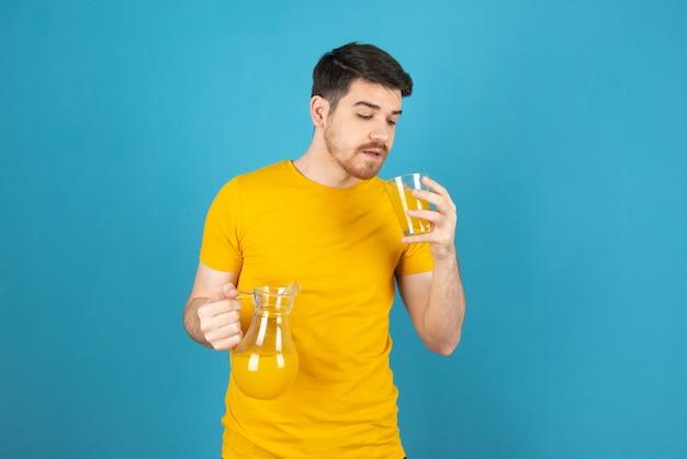 Jonge knappe kerel die vers sap probeert te drinken.
