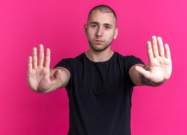 Jonge knappe kerel die zwart t-shirt draagt - geïsoleerd op roze background
