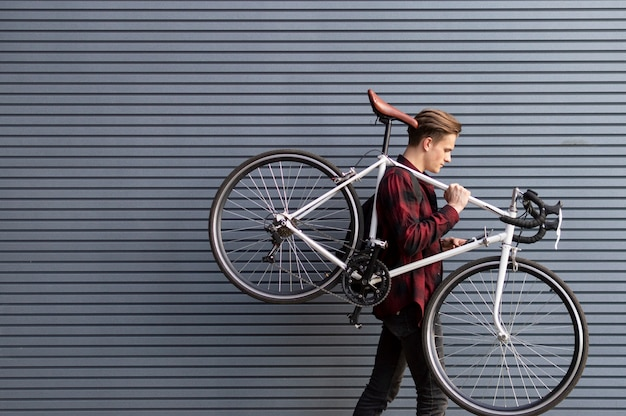 Jonge knappe kerel draagt een gebroken fiets op zijn schouders tegen de muur