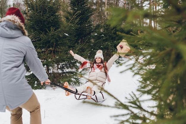 Jonge knappe kerel heeft plezier met het sleeën van zijn vriendin met geschenken in een winternaaldbos. een park met kerstbomen op de achtergrond. kerststemming. verven.