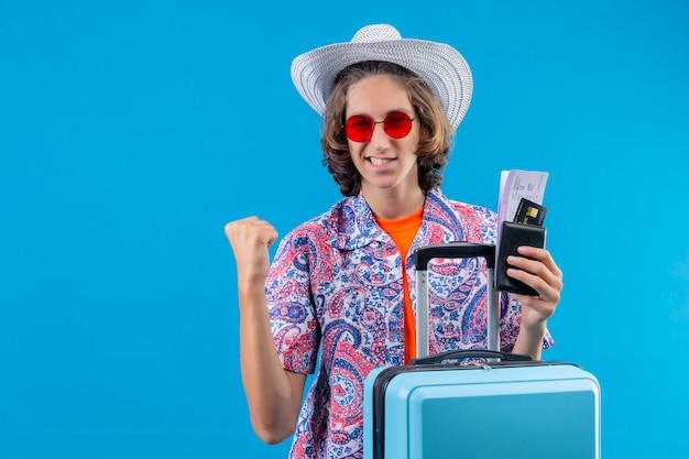 Jonge knappe kerel in de zomerhoed die rode zonnebril dragen die reiskoffer en vliegtickets houden die opgewekt kijken en gelukkig vuist opheffen na een overwinning die zich verheugt over zijn succes dat zich over blauwe ba bevindt