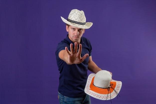 Jonge knappe kerel in de zomerhoed een andere hoed houden die zich bevindt met open hand die eindegebaar met ernstig gezicht over purpere achtergrond maken