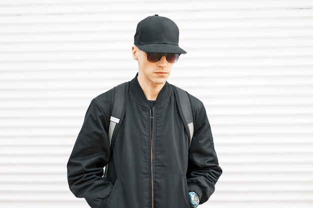 Jonge knappe kerel in een zwart jasje met een honkbalpet en een rugzak dichtbij een witmetalen muur