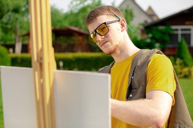 Jonge knappe kerel in gele zonnebril kunstenaar schilderen op canvas