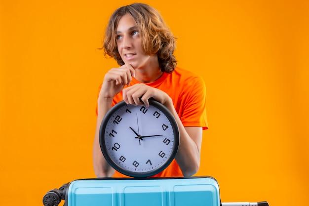 Jonge knappe kerel in oranje t-shirt die zich met de holdingsklok bevinden die van de reiskoffer opzij met peinzende uitdrukking kijken die zich over gele bakground bevinden