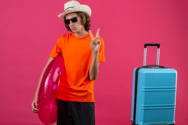 Jonge knappe kerel in oranje t-shirt die zwarte zonnebril draagt die opblaasbare ring houdt die zich met reiskoffer bevindt die op zoek zelfverzekerd overwinningsteken toont over roze achtergrond