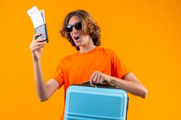 Jonge knappe kerel in oranje t-shirt die zwarte zonnebril draagt die vliegtickets en reiskoffer houdt die verbaasd en gelukkig status over gele achtergrond kijkt