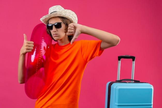 Jonge knappe kerel in oranje t-shirt en zomerhoed met zwarte zonnebril met opblaasbare ring ontevreden duimen op en neer met negatieve uitdrukking op gezicht staande met reizen s tonen