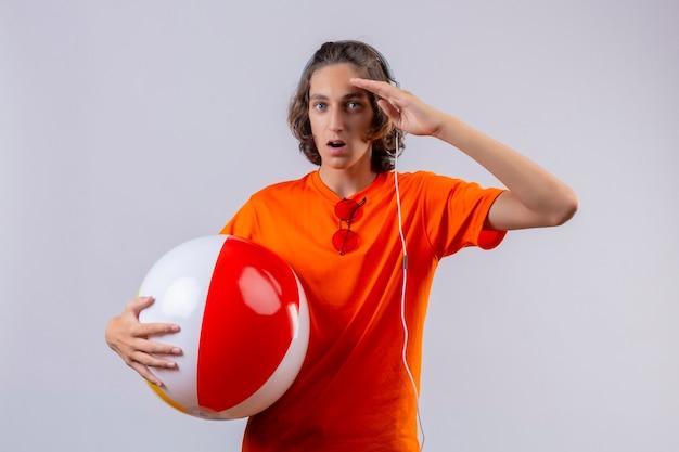 Jonge knappe kerel in oranje t-shirt met opblaasbare bal met koptelefoon op zoek verrast staande met hand in de buurt van hoofd op witte achtergrond
