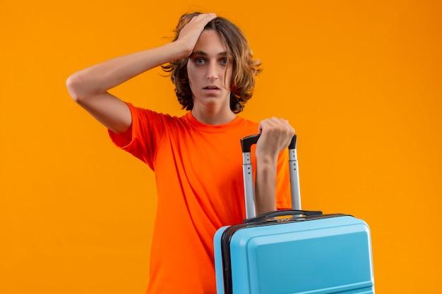 Jonge knappe kerel in oranje t-shirt met reiskoffer staande met hand op hoofd voor fout op zoek verward onthoud fout op gele achtergrond