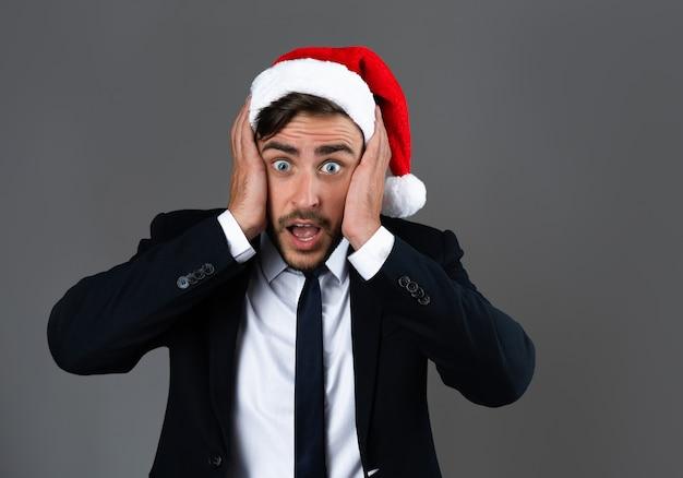 Jonge knappe kerel in pak en kerstmuts zeer verrast met handen op de wangen