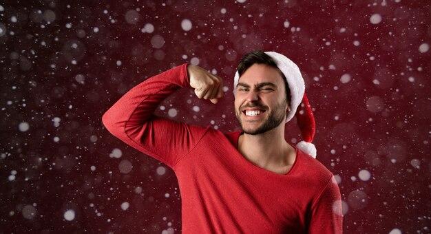 Jonge knappe kerel in rode trui en kerstmuts