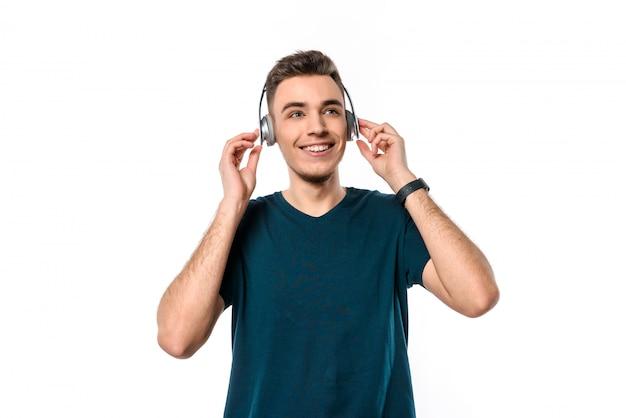 Jonge knappe kerel met hoofdtelefoons het luisteren muziek