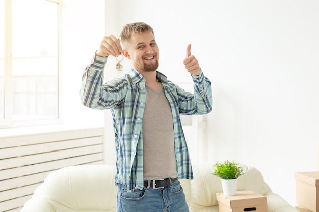 Jonge knappe kerel toont de sleutels van zijn nieuwe appartement en duimen opdagen terwijl hij in de