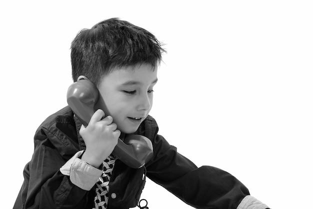 Jonge knappe kleine jongen geïsoleerd tegen een witte muur in zwart-wit