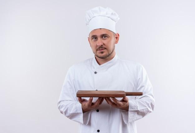 Jonge knappe kok die in de scherpe raad van de chef-kok eenvormige holding geïsoleerd op witte ruimte kijkt