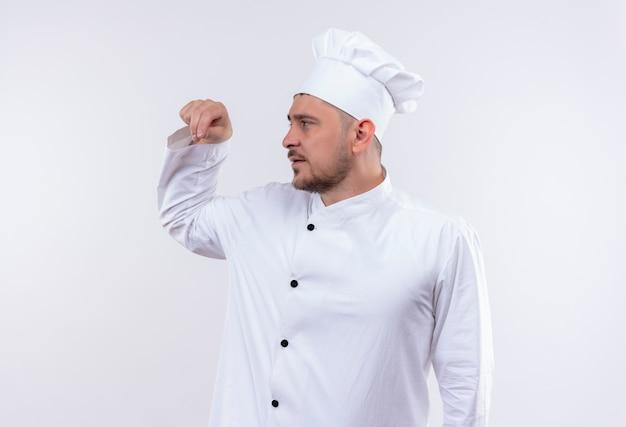Jonge knappe kok die in eenvormig chef-kok zout morst die kant bekijkt die op witte ruimte wordt geïsoleerd