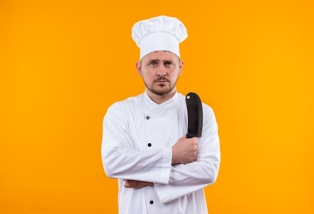 Jonge knappe kok die in het hakmes van de chef-kok het eenvormige holding geïsoleerd op oranje ruimte kijken Gratis Foto