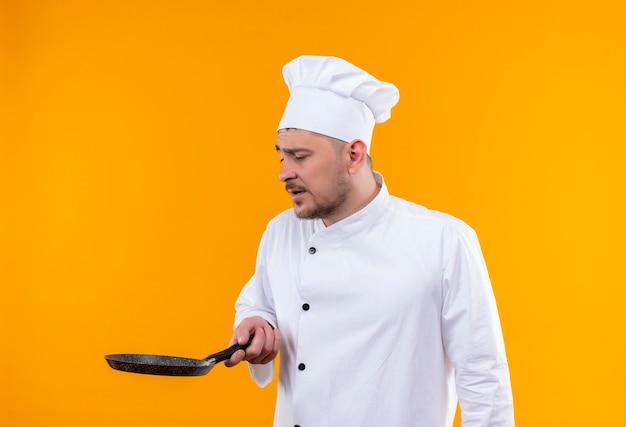 Jonge knappe kok in chef-kok uniform houden en kijken naar koekenpan geïsoleerd op oranje ruimte
