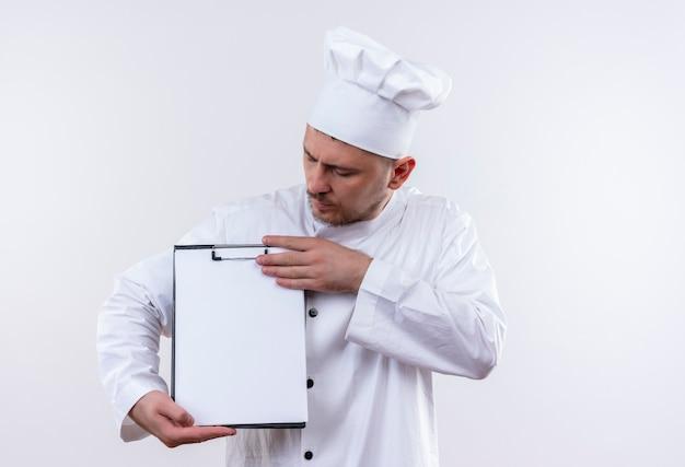 Jonge knappe kok in chef-kok uniform klembord houden en bekijken op geïsoleerde witte ruimte