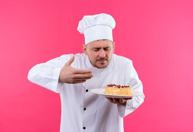 Jonge knappe kok in chef-kok uniform plaat van cake houden en snuiven het geïsoleerd op roze ruimte