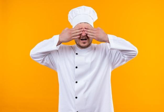 Jonge knappe kok in chef-kok uniform zijn ogen sluiten met handen met open mond geïsoleerd op oranje ruimte