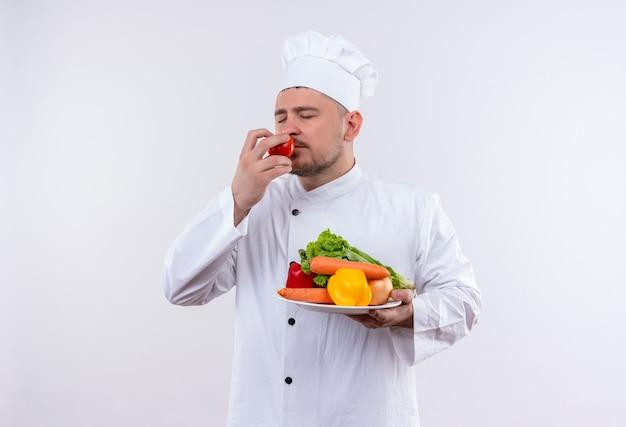 Jonge knappe kok in chef-kok uniforme bedrijf plaat met groenten en tomaat snuiven met gesloten ogen op geïsoleerde witte ruimte