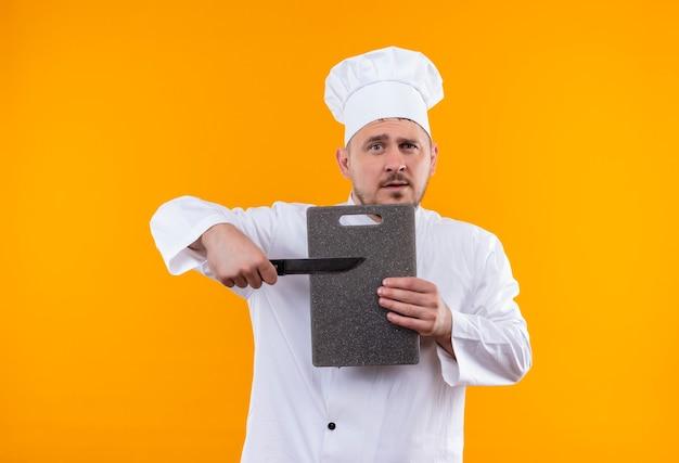 Jonge knappe kok in chef-kok uniforme bedrijf snijplank en mes geïsoleerd op oranje ruimte