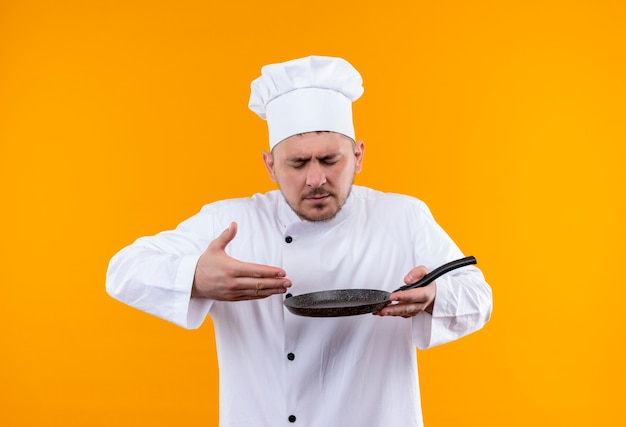 Jonge knappe kok in chef-kok uniforme koekenpan houden en snuiven geïsoleerd op oranje ruimte