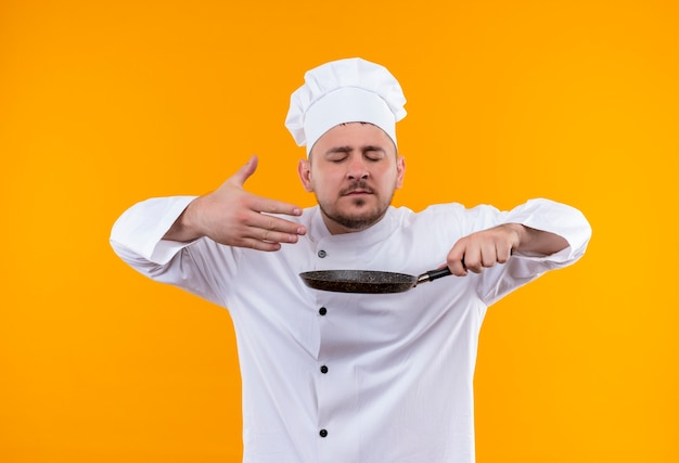 Jonge knappe kok in chef-kok uniforme koekenpan houden en snuiven met gesloten ogen en opgeheven hand geïsoleerd op oranje ruimte