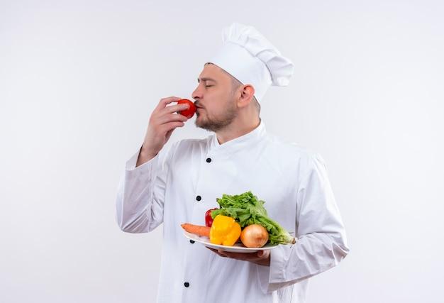 Jonge knappe kok in chef-kok uniforme plaat met groenten houden en tomaat op mond zetten met gesloten ogen geïsoleerd op witte ruimte