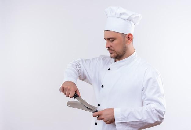 Jonge knappe kok in eenvormige chef-kok die mes en hakmes wrijft dat op witte ruimte wordt geïsoleerd