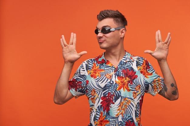 Jonge knappe kortharige man in zwemmen bril kijken op zijn opgeheven handpalmen met vingers bij elkaar, staande