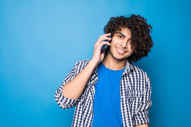 Jonge knappe krullende mens die op de telefoon spreekt die op blauwe muur wordt geïsoleerd