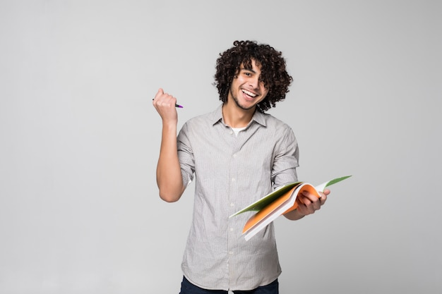 Jonge knappe krullende studentenmens met notitieboekjes over geïsoleerd op witte muur