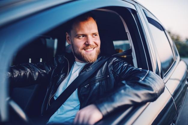 Jonge knappe lachende bebaarde blonde blanke man in lederen jas poseren in zijn moderne auto.