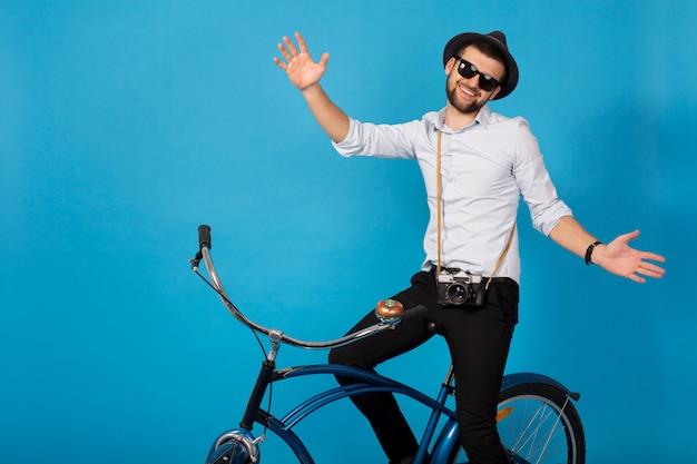 Jonge knappe lachende gelukkig man reizen op hipster fiets, poseren op blauwe studio achtergrond, shirt, hoed en zonnebril dragen