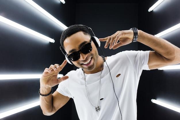 Jonge knappe lachende hipster zwarte man in witte outfit luisteren naar muziek op koptelefoon en dansen in hiphopstijl in disco nachtclub, plezier